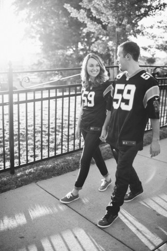 Couple wearing panthers jersey walking along the sidewalk