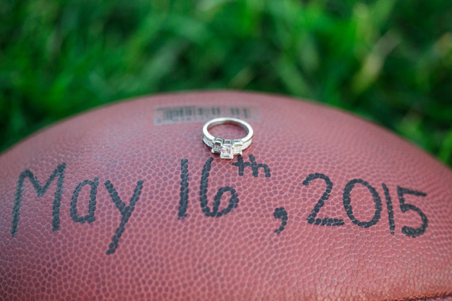 A football with a wedding date written on it and an engagement ring on top
