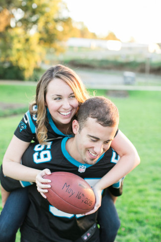 Girl on her fiance back holding a football for engagement photos