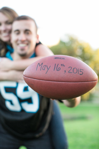 A couple wearing Carolina Panther jerseys holding out a football with wedding date on it