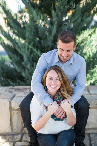 couple sitting on brick wall smiling