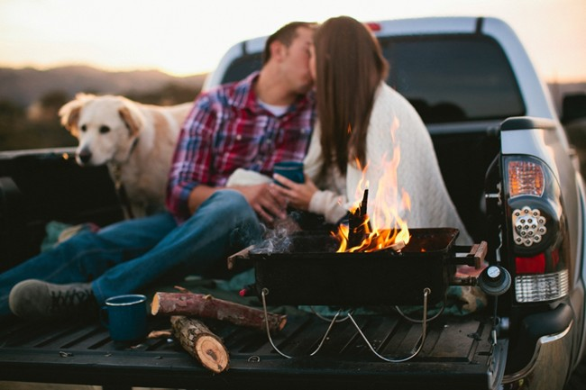 bride and groom in back of pickup truck with their dog and a campfire stove