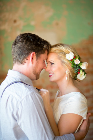 styled shoot couple: she with a floral wreath crown, he with suspenders