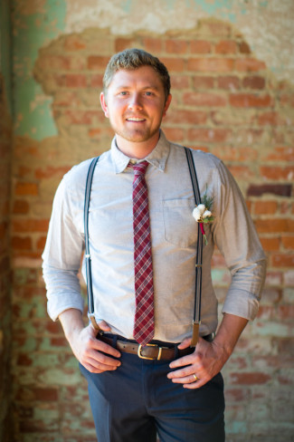 Groom wearing a dress shirt, plaid tie and suspenders with a cotton boutonniere