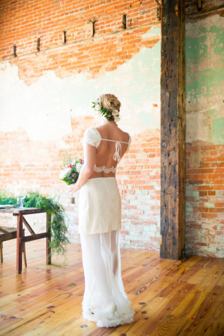 Bride wearing a white Mena Garcia gown with flowers in her hair and a brick wall behind her