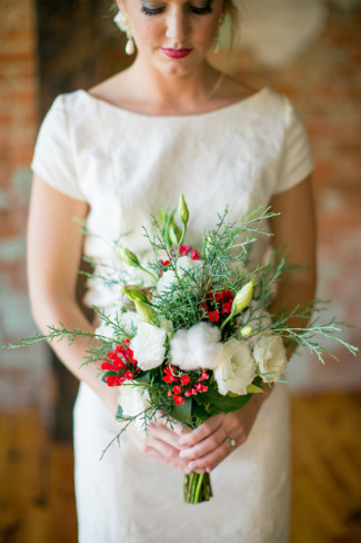 Bride carrying a bouquet of green, white and red flowers and cotton accents