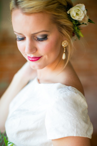 Bride wearing a Mena Garcia gown with white flowers in her hair and drop pearl earrings