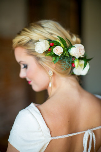 Bride with her hair braided and white and pink roses going down the side of her hair