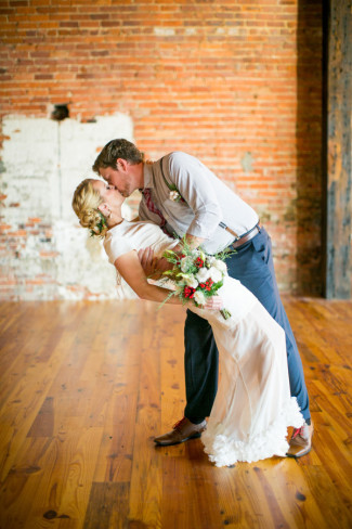 Groom dunking bride for a deep kiss on wood floor and brick background