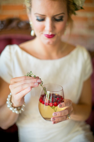 Bride holding a wine glass with sangria and red cranberries