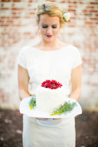 Bride holding a cake stand with 1 tier white cake with red flowers on top