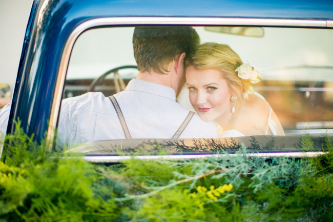 bride and groom sitting in a vintage truck driving away