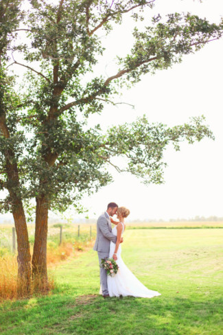 Bride and groom in an open field capture by Lana Jenae Photography