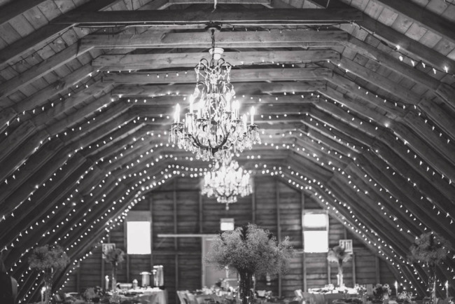 Chandeliers and white lights for rustic bard wedding reception