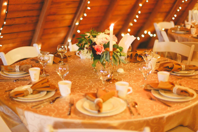 Round reception table with gold table cloth and floral center piece