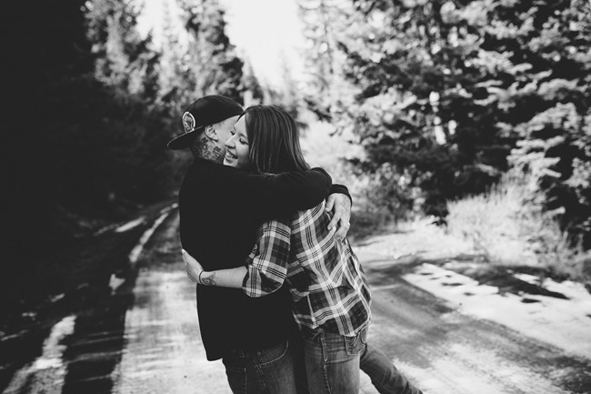 black and white photo of engaged Couple embracing in forest