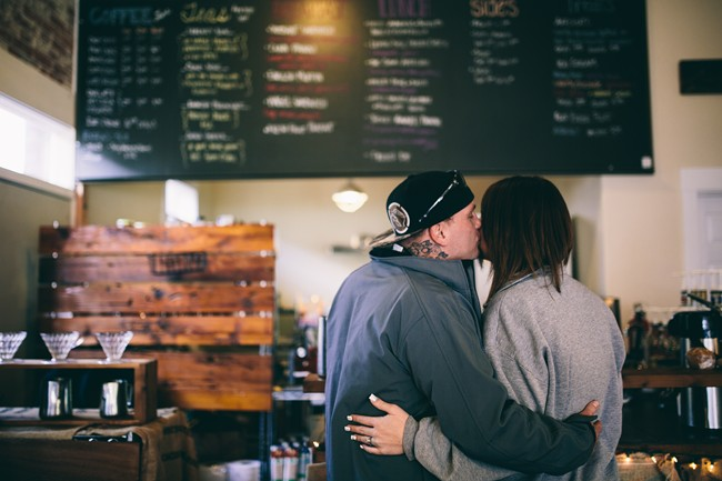 Couple kissing at coffee counter of Gathering Grounds Cafe in Oregon
