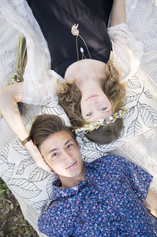 Modern day hippie couple laying on a blanket outside looking up at camera