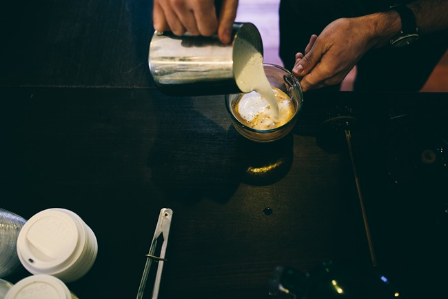 Barista pouring latte at Gathering Grounds Cafe