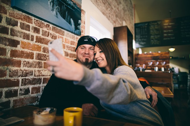 Couple taking selfie during engagement session at Gathering Grounds Cafe