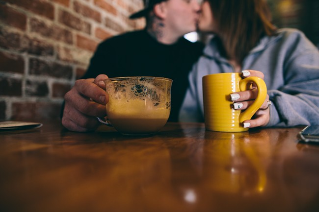 Couple kissing during engagement session at Gathering Grounds Cafe