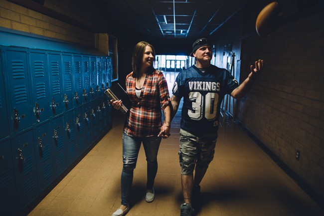 Couple walking down their high school hall way carrying books and a football