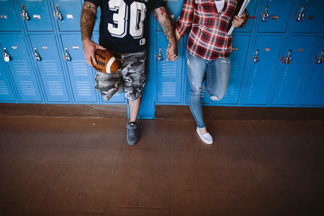 Couple leaning up again lockers for engagement session
