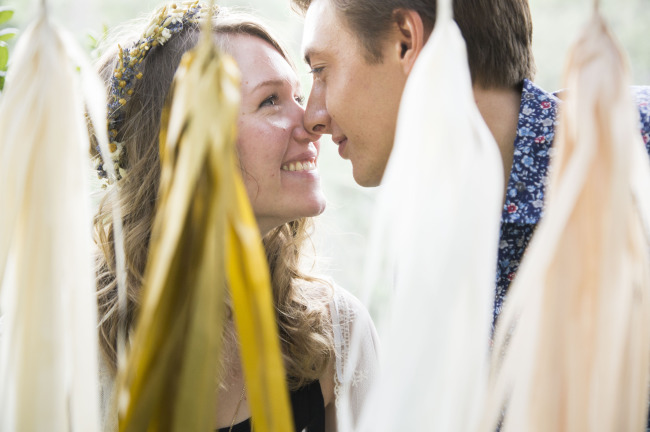 Couple nose to nose standing behind gold, blush pink and cream garland