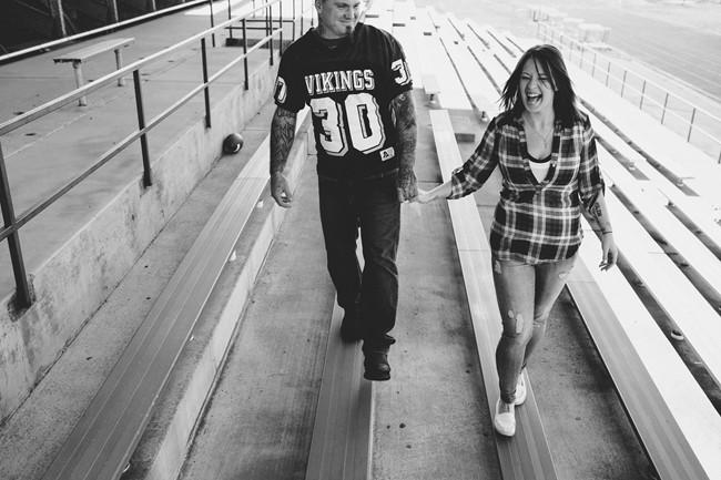 Couple walking hand in hand along bleachers