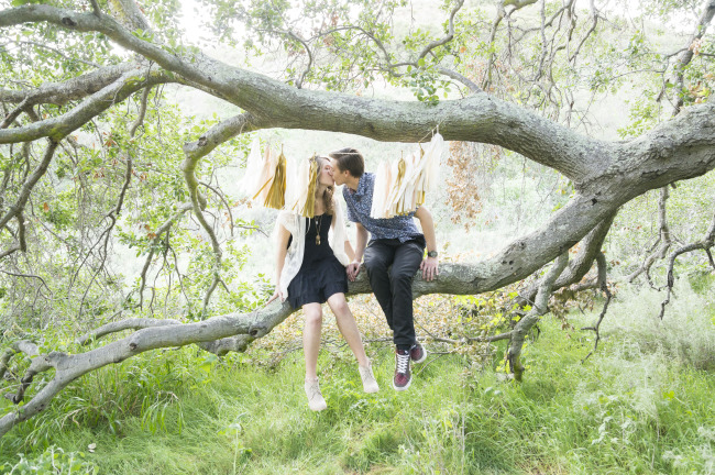 Couple sitting and kissing in a tree in Trabuco Canyon in a modern day hippie shoot