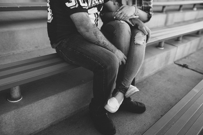 Coupe sitting together on bleachers for engagement session