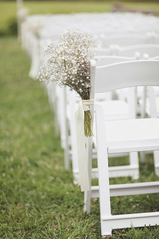 White chairs for outdoor wedding ceremony with baby's breath on the chair