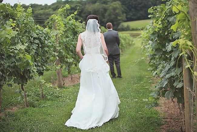 Bride walking up to groom in vineyard for first look