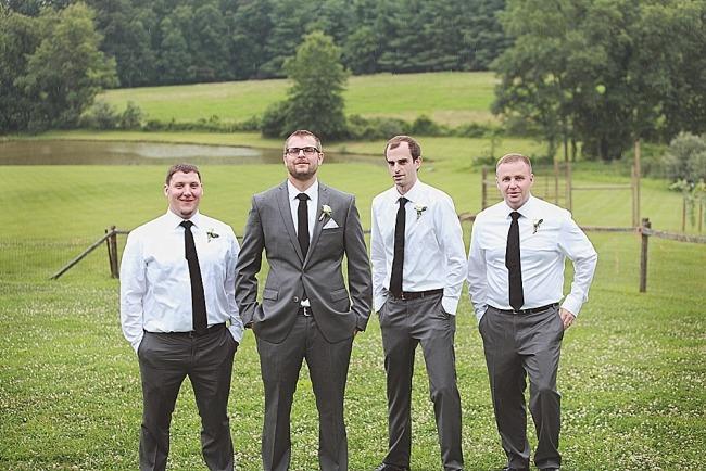 Groom standing with groomsmen wearing gray suits and black ties