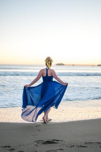 Girl walking along Avila Beach in a blue halter dress with bare feet
