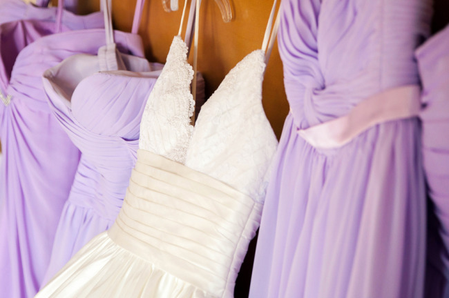 Purple bridesmaids dresses hanging up with a Maggie sottero spaghetti strap dress