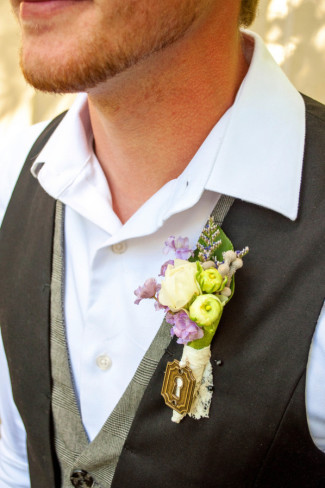 Groom wearing a vest with a purple, white and yellow boutonniere