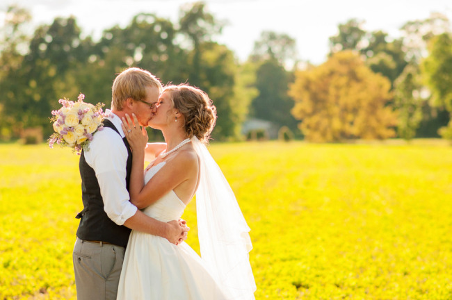 Bride and groom kissing in a yellow field captured by Kasey and Ben - PMPS Photography LLC
