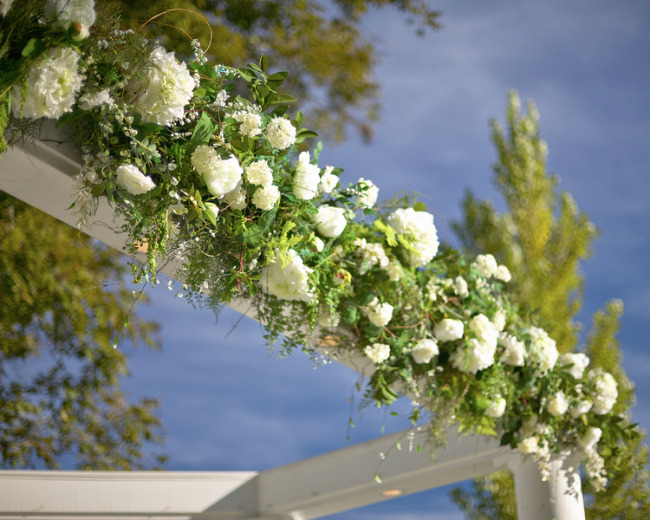White flowers and greenery over outdoor wedding ceremony arch way