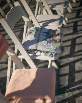 Outdoor wedding ceremony white folding chairs with blankets folded on them
