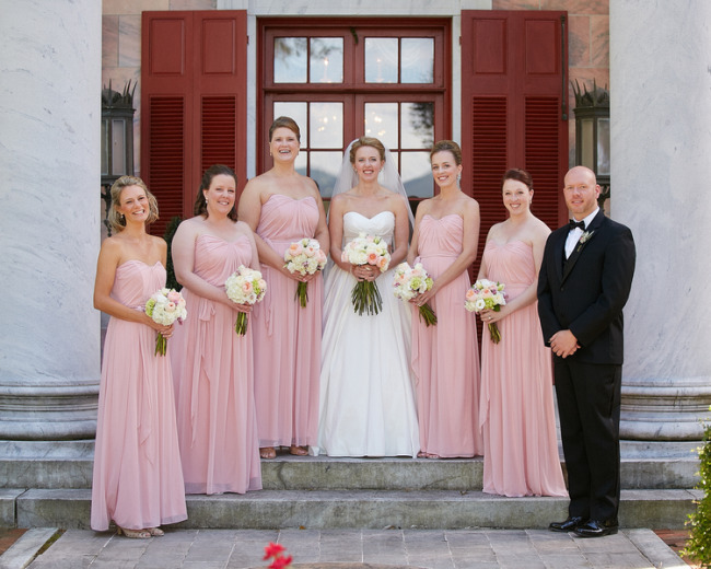 Bride standing with bridesmaids wearing blush pink gowns