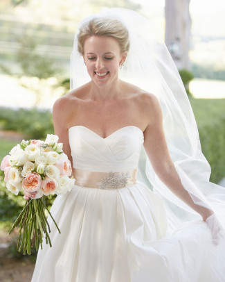 Bride wearing sweet heart neckline gown with cream color sash belt