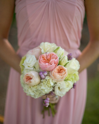 Bridesmaid wearing blush pink gown and holding pink, white hydrangea and peach flower bouquet