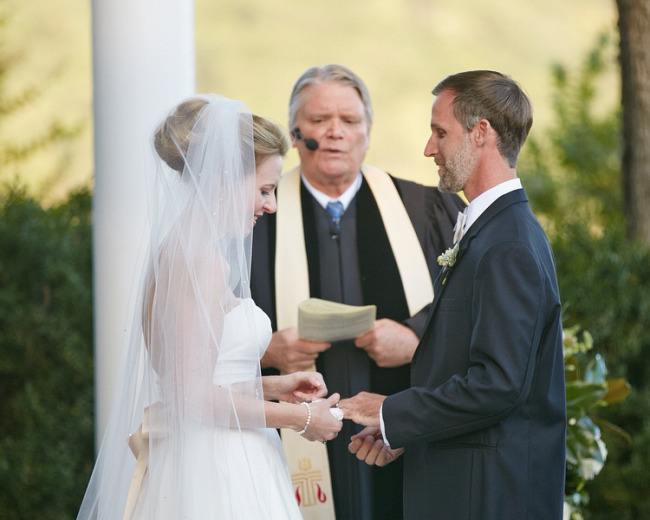 Bride and groom exchanging rings during ceremony at Tate house Mansion
