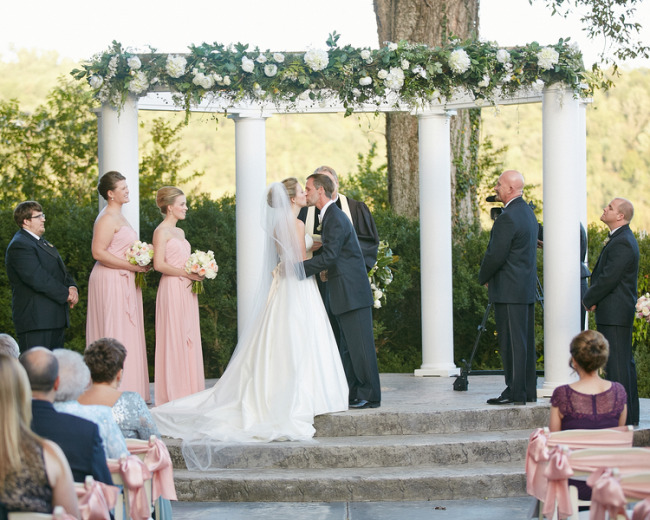 Bride and groom kissing during pink colored wedding ceremony