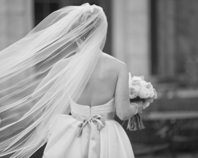 Black and white photo of a bride wearing a chapel length veil