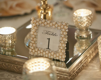 Silver wedding reception center piece with candles and silver pearl framed table number