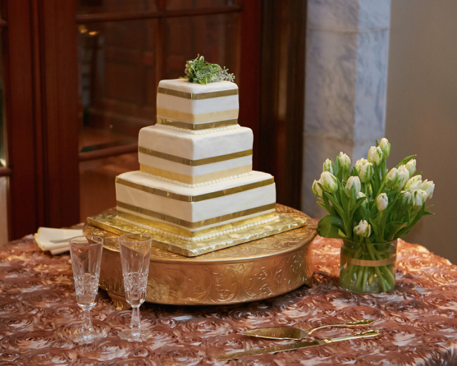 3 tier square wedding cake with gold and sage colored edging