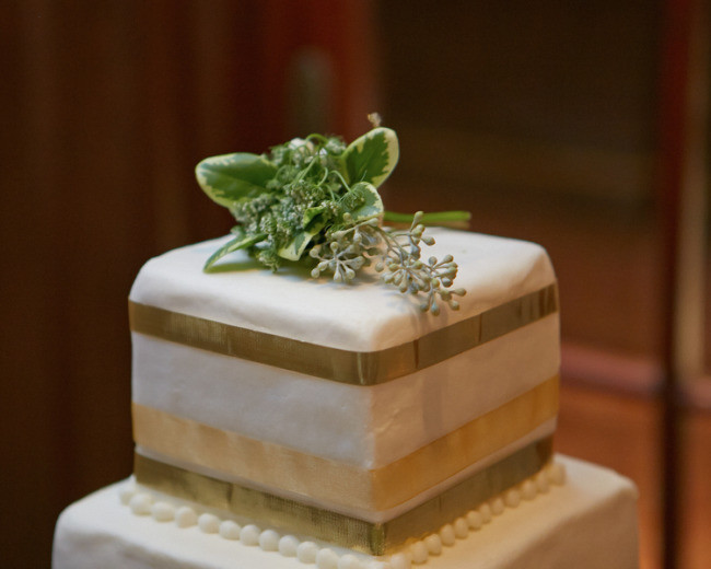 square wedding cake with sage and gold pipping