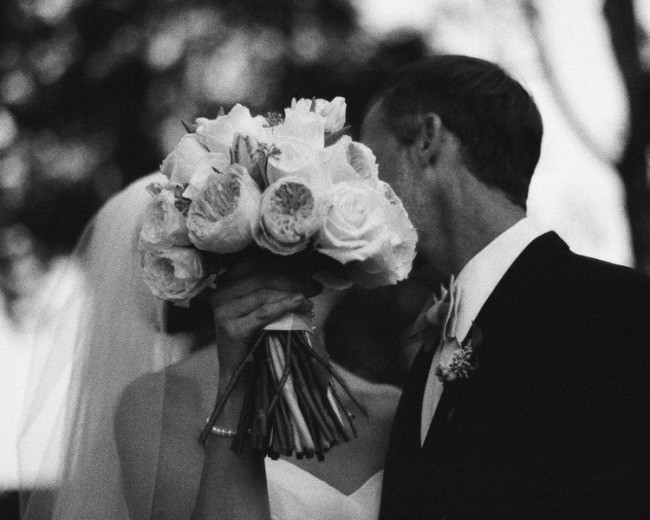 black and white photo of Bride and groom kissing behind bridal bouquet
